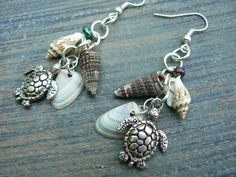 "If you like wearing things that are different and have people asking you ""where did you get that? "" Then you'll love this, and everything from Gilded in Gypsy! It's like you're at the beach! The silver toned earring hooks are adorned with an adorable litttle sea turtles and have three different tiny seashells along with a peacock colored bead for a little irridesence in the light, ADORABLE! Perfect for the beach or that mermaid cosplay outfit!This piece dangles about 1 1..."