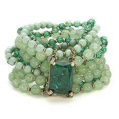 From charmandchain.com an elastic, multi-band bracelet composed of various hues of subtle green beads and one rectangular accent piece that also serves so clasp all the strands together.