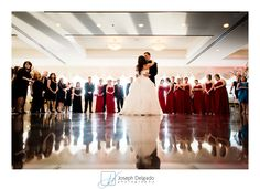 Creative first dance photographs are some of my favorite to create.  The shiny dance floor made for a nice reflection. The photograph took place at The Mill in Spring Lake Heights.   Wedding Venues at the Jersey Shore make for wonderful locations to have a wedding ceremony and/or reception.  In this wedding reception photograph, the red bridesmaids dresses are also on display as well as the beautiful wedding dress.