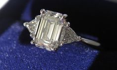 The center stone is an emerald cut, 1.02 carat diamond, GIA certified, H color, VS1 clarity, depth 67.2% and table 58%. The measurements for the center stone are 7.01 x 4.81 x 3.20 with a length to width ratio of 1.46. The symmetry received a VG rating and the polish an EX rating. No fluorescence, pointed culet, and a slightly thick to thick girdle. The side stones consist of two trillion cut diamonds, 0.22 total carat weight, H color, VS clarity.