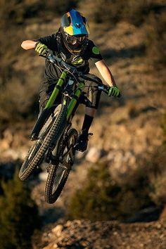 Women biker jumping with a downhill mountain bike.- Women biker jumping with a d. - Women biker jumping with a downhill mountain bike.- Women biker jumping with a downhill mountain bi - All Mountain Bike, Mountain Biking Quotes, Folding Mountain Bike, Mountain Biking Women, Mountain Bike Helmets, Downhill Bike, Mtb Bike, Rollers, Motocross