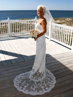 A Simple Dress and chapel length veil with a pretty tiara!  Love the backdrop of the ocean!