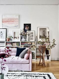 Simply pretty. Casual display of photos/art, books, flowers, plants in an open case with a soft pink sofa. https://m.domino.com/content/Magazine