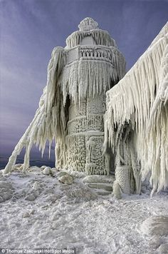 A lighthouse stands frozen still after a big storm in St Joseph, Michigan
