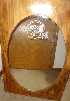 "Beautiful hand-crafted mirror has a lovely wooden finish with the Packers' logo and football etched on the glass.  Measures 24 X 36"".  Perfect for your Packer room!"