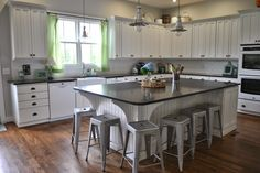 Pretty farmhouse kitchen with white painted cabinets, apron sink, Ikea pendant lighting, island industrial stools
