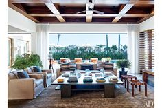 In George Clooney's Los Cabos, Mexico, living room, a slipcovered sofa and armchairs and a pair of stools by Casamidy are grouped around a cocktail table by SL Westwood Design. The home was designed by Legorreta + Legorreta.
