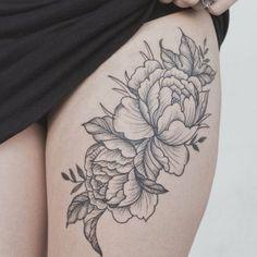 un gros tatouage fleurie noir sur la cuisse
