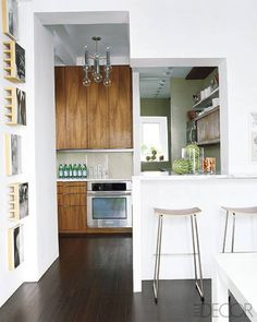 The kitchen's  custom-made walnut cabinetry  is by William Feeney Studio,  the oven is by Electrolux, and  the stools are from White Furniture Industries.   - ELLEDecor.com