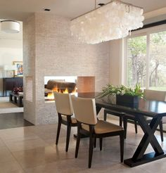 A contemporary scene, this fireplace connects and separates the dining and living room areas with ease, interest and stylish delight