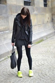 黒のライダースと黒のパーカーとスニーカーを着る女性
