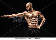 Strong bald bodybuilder with six pack. Strong bodybuilder man with perfect abs, shoulders,biceps, triceps and chest, personal fitness trainer flexing his muscles in blue, red smoke