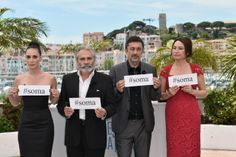 """At the photocall for Turkish film Winter Sleep, actor Demet Akbag, director Nuri Bilge Ceylan, and actors Haluk Bilginer and Melisa Sozen (left to right) hold signs reading """"Soma"""" to pay their respects to the 284 Turkish miners who died following an explosion. Photograph: Bertrand Langlois/AFP/Getty Images"""
