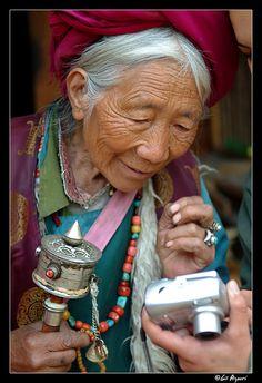 Elderly Tibetan woman looking at her portrait on the back of a digital camera.   Meili Xueshan mountain range ,Deqin 'Shangi-La'.
