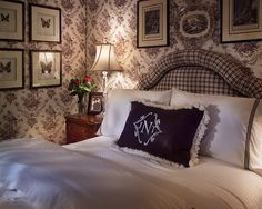Upholstered chocolate and white toile walls mixed with crisp white linens add intimacy and charm to this small guest bedroom.