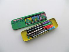 Features! > awesome 1990s TMNT pencil case/desk supply storage > bright green metal > open lid to reveal removable yellow tray > lift up tray - lined bottom compartment > fits standard pens, pencils, and various kinds of school supplies  Label: © 1990 Mirage Studios USA, Taiwan Tai Sing Co., Ltd.  Length: 8.5 Width: 2.4 Height: 1  In very good vintage condition! Shows surface wear characteristic of age and previous use. Some scuffs and scratches on back and front, with min...