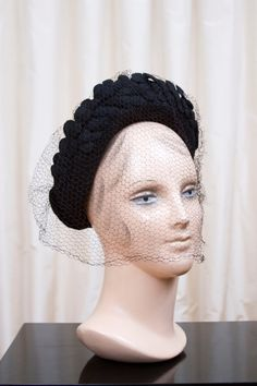 1940s black hat sits on the crown of your head and comes up with a halo taller in the front. Top edge decorated in little heart shaped petals or