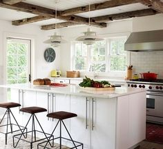 Exposed beams with exposed white wood ceiling. Also has white high gloss lacquered cabinets