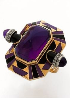 An Art Deco amethyst ring, circa 1925. Centring a large amethyst surrounded by purple and black patterns in enamel, flanked by two projecting bullets, each set with an amethyst cabochon and rose-cut diamonds, mounted in platinum.