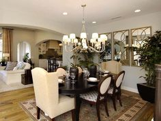 Formal Yet Open Dining Room: This transitional dining room opens up to the great room and kitchen, but the arched soffit helps define the space. Dark espresso furniture and a large area rug and chandelier add formal touches. From HGTVRemodels.com