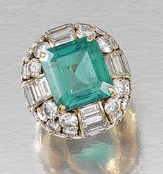 EMERALD AND DIAMOND RING, MONTURE CARTIER. Centring on a step-cut emerald, to a mount of bombé design set with brilliant-cut and baguette diamonds, size J ¾, inscribed Cartier Mtg.