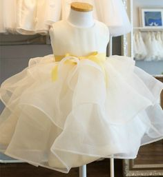 3 Tier Dress--Made To Order - High Quality Cute & Chic Round Neckline Sleeveless Knee Length 3 Tier Little Girl Dress With Yellow Sash Belt - Perfect dress for birthday party, wedding, baptism, photo shoot or any special occasion. Material: Cotton, soft polyester fabric, satin. Available from 1 - 12 years. Color: White. Please do compare your little girl measurements with our size chart below or you may leave a note your little girl's height, bust and waist measurements so we can process it…