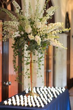 White hybrid delphinium arrangement with ivy and seeded eucalyptus