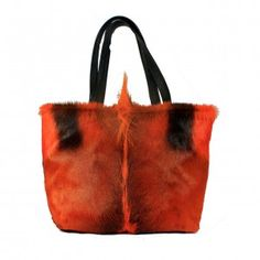 """Orange dyed Hair on Springebok hide Tote. Brown leather handles. Interior with 3"""" leather top and orange cheetah print lining One leather zippered interior pocket and 2 open hand beaded, fabric pockets. Leather strap with brass toggle for easy to find keys. Magnetic closure. 18""""wide x 12"""" high with 5"""" soft bottom."""