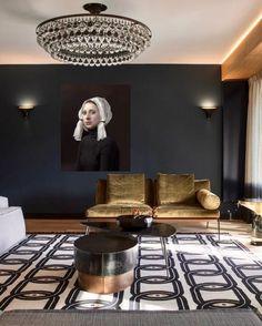 deco salon design avec des meubles en couleur tabac, tableau style XV ème siècle, grand luminaire rond en forme de tambour avec des grandes pampilles en cristal, tapis avec des motifs chaines en noir et blanc