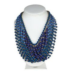 Layered necklace with strands of navy blue beads.  Product: NecklaceConstruction Material: Zinc, tin, gold plated and plastic beadsColor: NavyFeatures:  Lobster claw closure4 Exension Dimensions: 3 H x 15 WCleaning and Care: Keep away from any forms of moisture, lotions, or chemicals. Keep in plastic baggies to avoid tangling and tarnishing.