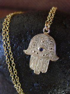 """Vis à Vis Hamsa Bronze Necklace The Vis à Vis Hamsa Necklace represents this Arabic symbol through a simple and elegant design. Hamsa translates to """"Five"""" and is also referred to as the Hand of Fatima"""