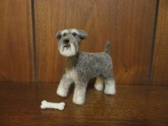 This little Schnauzer is hand-made out of 100% sheep wool. Its eyes are made of glass. The Schnauzer also comes with its own little toy bone which is also needle felted. It is also gently posable as it has a wire armature! This sculpture is about 3.75 inches (9.52 cm.) long from nose to tail, and 3.5 inches (8.89 cm.) tall from the top of its head to its feet. It is for 1:6 dollhouse scale.  This dog took many hours of careful, loving work to be created through a process called…