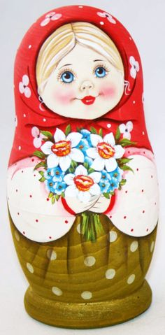 Pretty matryoshka (Russian nesting doll) in a red shawl with a bouquet in its hands.