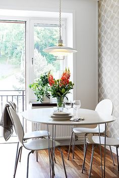 Eat in kitchen dining.  Cute white table and modern chairs.  Gray wallpaper and pendant light.  Love the glass door and window that lets in so much light. http://cococozy.com
