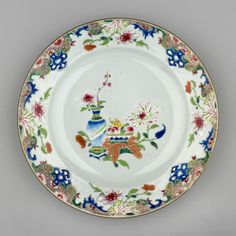 A pair of Chinese plates with a vase of flowers and a dish of fruit in the centre. Border with shaped reserves and flowers. Famille rose enamels with blue.