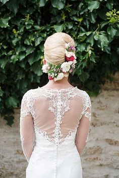 Pretty wedding dress back detail and up do hair style. Love the added flowers to the brides hair.