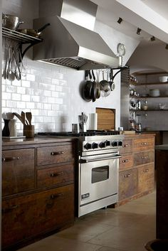 kitchen with rustic wood cabinets, subway tile, stainless steel.