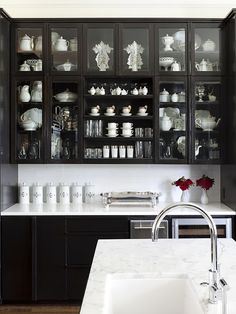white dish collection in a black cupboard...