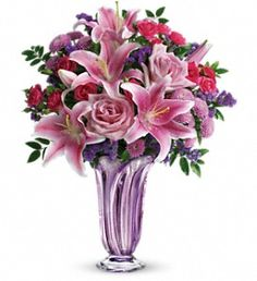 Lavender Grace Bouquet ~  her with lavender! Hand-delivered in a beautiful limited-edition, hand-blown art glass vase, this breathtaking bouquet of roses and lilies will make her feel like the extra special person she is on Mother's Day.  This lovely bouquet includes pink roses, hot pink spray roses, pink oriental lilies, lavender button spray chrysanthemums, purple sinuata statice, and fresh green huckleberry. Delivered in a Lavender Grace vase.