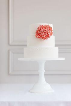 Tarta de bodas simple y elegante con una flor gigante en color coral