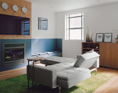 In the living room, a Dublexo sofa and ottoman by Innovation Living was sourced from Zinc Details. The rug is from Ikea; the Kozy Heat gas fireplace is clad in gray tilework and knotty cedar planks. The clocks are from Muji and the posters are from Paper Jam Press.