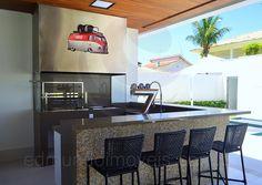 Sob o alpendre, o espaço gourmet conta com churrasqueira em aço inox, chopeira e recebeu o mesmo padrão de acabamentos da cozinha.