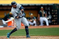 Nelson Cruz Photos Photos - Nelson Cruz #23 of the Seattle Mariners hits an RBI sacrifice fly against the Oakland Athletics during the third inning at the Oakland Coliseum on April 22, 2017 in Oakland, California. The Oakland Athletics defeated the Seattle Mariners 4-3. - Seattle Mariners v Oakland Athletics