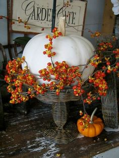 White pumpkin framed with bittersweet resting on a beautiful woven pedestal. Fall home decor inspiration for a farmhouse.