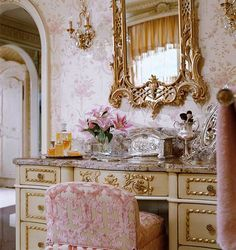 Gorgeous vanity in gold with pink velvet seat and wallpaper! Charles Faudree in Traditional Home.