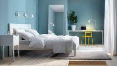 Minimalistisches Schlafzimmer auf wenig Raum u. a. mit NORDLI Bettgestell weiß, 3-teiligem DVALA Bettwäsche-Set weiß, NORDLI Ablagetisch weiß, MALM Ablagetisch weiß, REIDAR Stuhl gelb, HOVET Spiegel Aluminium, HELG Hängeleuchte, TISDAG LED-Wandleuchten weiß + ALHEDE Teppich Langflor in Elfenbeinweiß