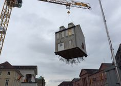A root system sprouts from the concrete foundations of this house installation that dangles from a crane above a construction site in Germany.