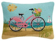Artist Suzanne Nicoll once again captures the warmth of a day beside the sea with her whimsical Sunshine and Pink Bicycle Beach Cottage 22 x 16 rectangle wool hooked Pillow.