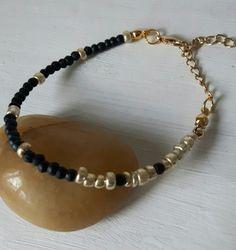 Armbandje van zwarte en goudkleurige rocailles. Met verlengkettinkje.