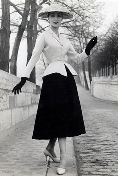 Christian Dior's New Look, 1947. As a reaction to the rationing of World War II the new look, using many metres of fabric, came into fashion. It was a return to the classic feminine shape, emphasising the bust and hips, with a tiny waist. I love how glamorous this looks with the tiny jacket and voluminous skirt.